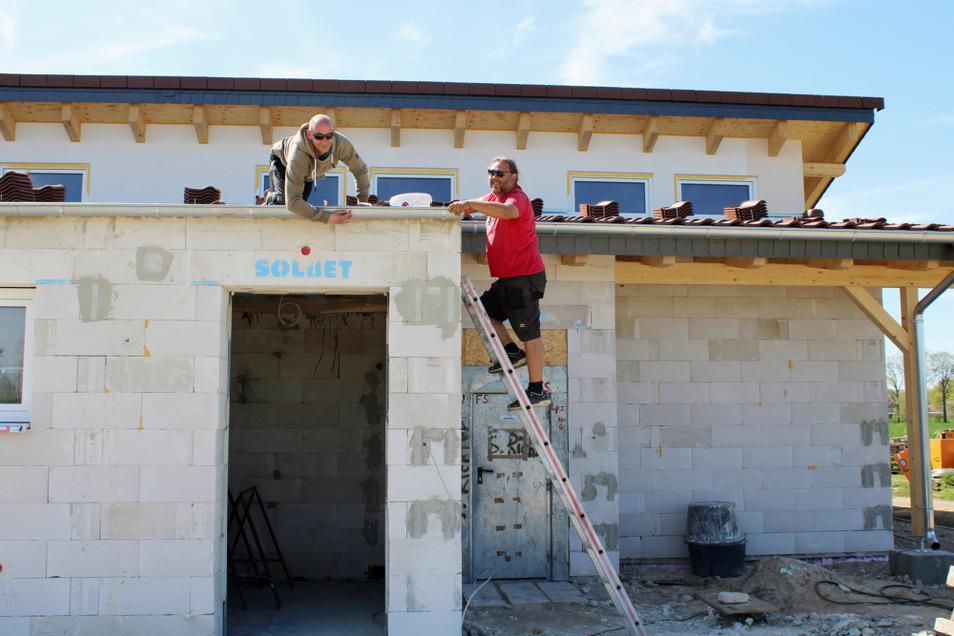 Carsten Nötzold (re.) und sein Mitarbeiter befestigen eine Dachrinnenhalterung am neuen Sanitärgebäude.