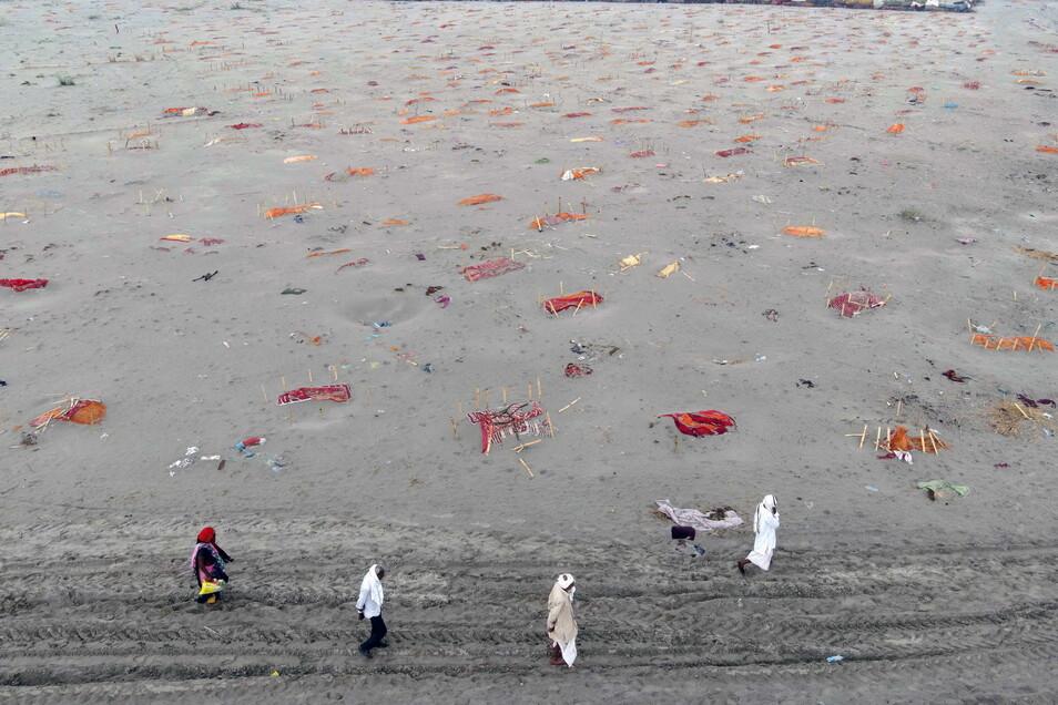 Solche Bilder gingen um die Welt: Gräber in der Nähe eines Einäscherungsplatzes am Ufer des Ganges sind mit safranfarbenen Tüchern bedeckt.