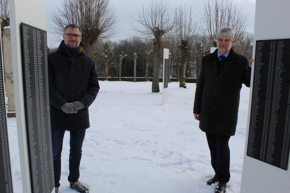 Sven Riesel (l.), Kommissarischer Stiftungsgeschäftsführer, und der Großschweidnitzer Bürgermeister Jons Anders, stehen vor den Gedenkstelen mit den Namen der Euthanasie-Opfer.