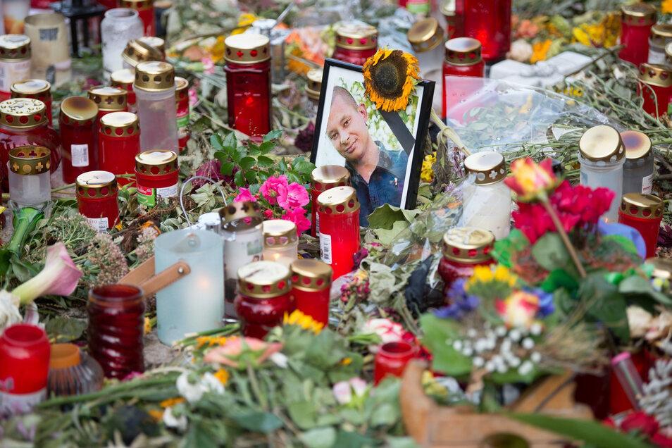 Ein Foto des Opfers steht am Tatort zwischen zahlreichen Blumen und Kerzen.