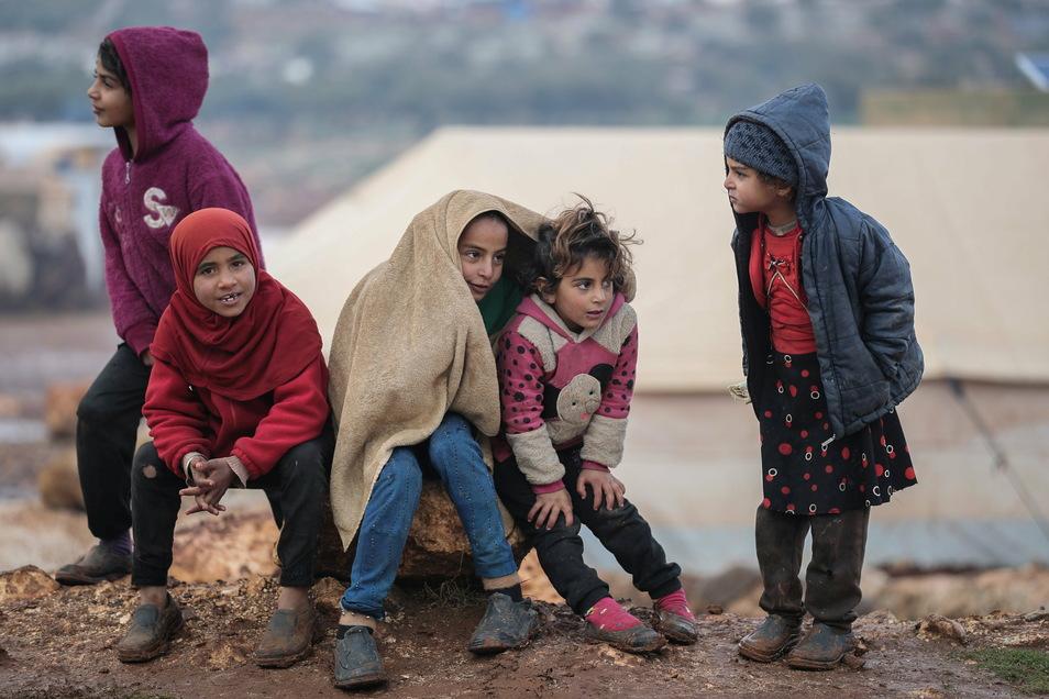 Syrische Kinder versuchen, sich bei kalten Wetterbedingungen in einem Flüchtlingslager für Binnenvertriebene warm zu halten. Die EU will nun erneut Hilfen für das Bürgerkriegsland sammeln.