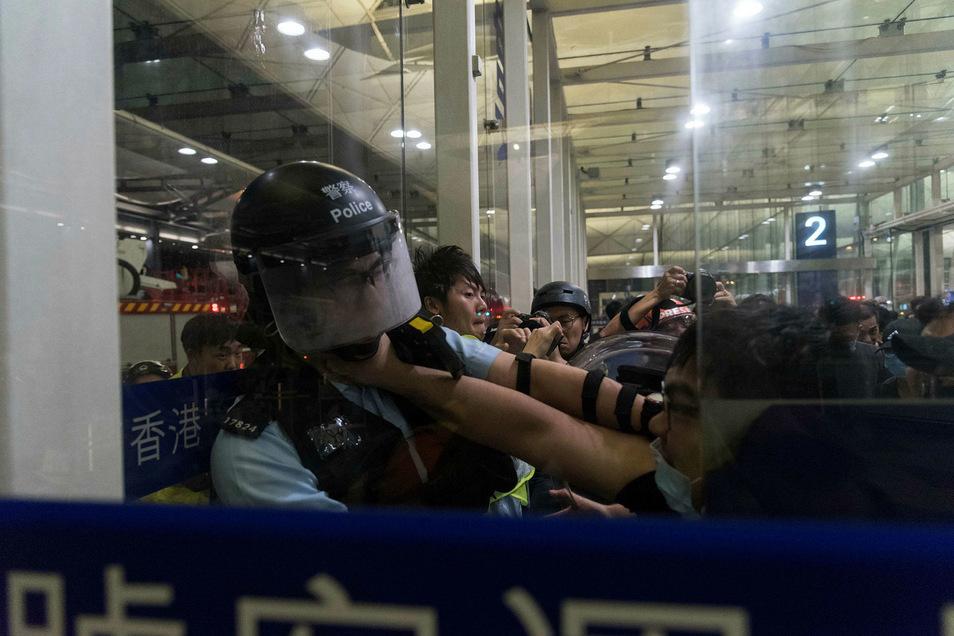 Demonstranten und Polizisten liefern sich trotz der Barrikaden im Flughafen eine gewaltsame Auseinandersetzung.