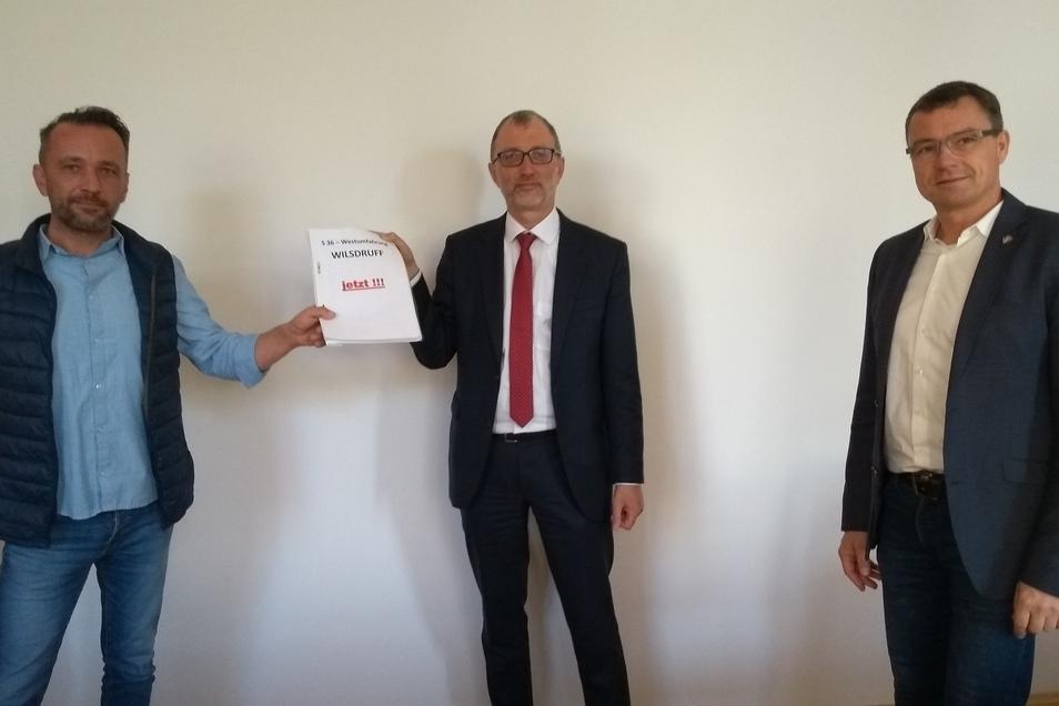 Übergabe mit Abstand. Oliver Köbe (links) überreicht die Unterschriften im Beisein von Bürgermeister Ralf Rother (rechts) an Godehard Kamps, dem Leiter der Abteilung Infrastruktur in der Landesdirektion.