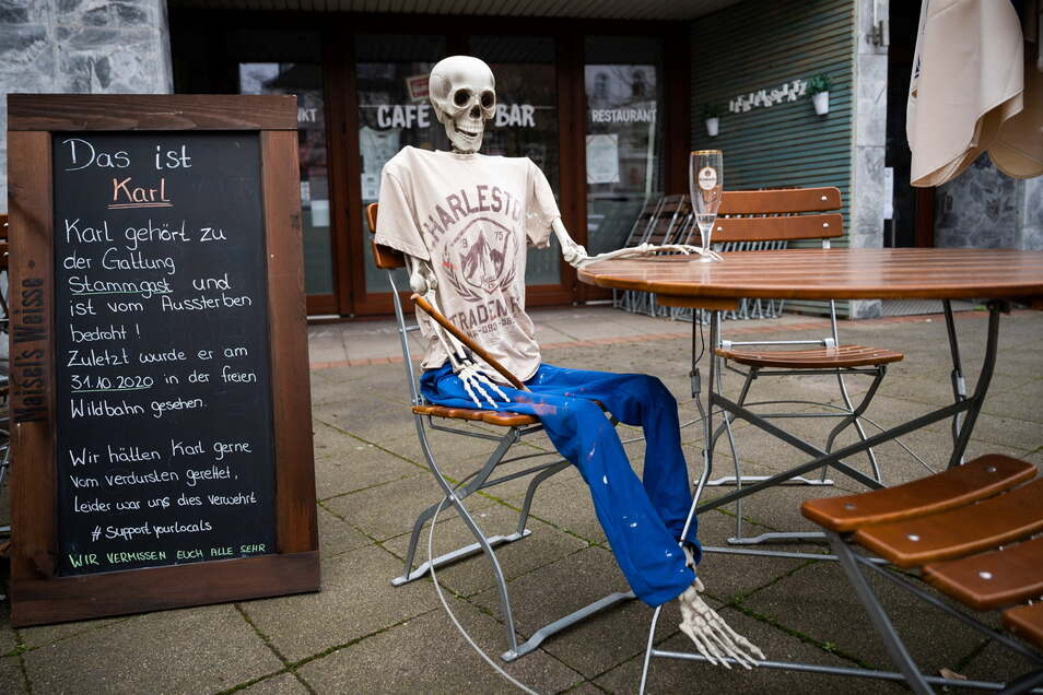 Ein Skelett sitzt Anfang März mit einem leeren Bierglas vor einem wegen der Corona-Pandemie geschlossenen Restaurant Hannover.