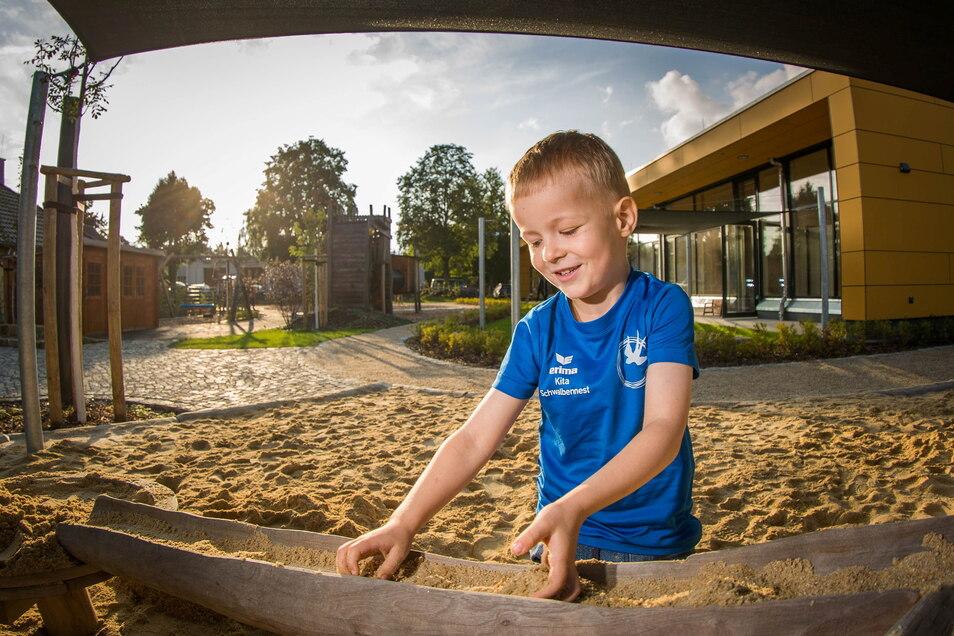 Der fünfjährige Kaleb probiert schonmal den Sandkasten aus. Er wird ab der kommenden Woche die neue Kita besuchen.