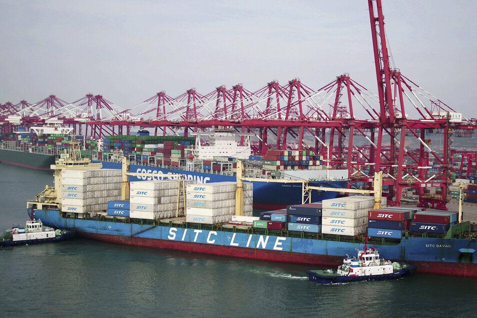 Zwei Lastkähne bringen ein Containerschiff zur Werft in Qingdao in der ostchinesischen Provinz Shandong (Symbolfoto).