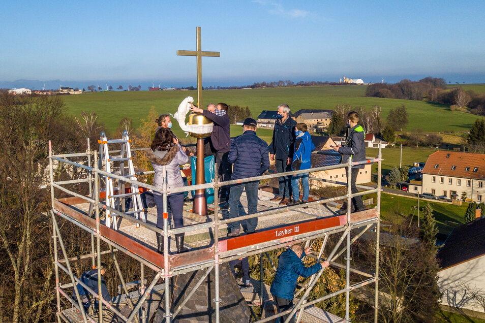 Die Handwerker haben dem Kirchturm von St. Ägidien in Altenhof eine neue Kugel und ein neues Kreuz aufgesetzt.