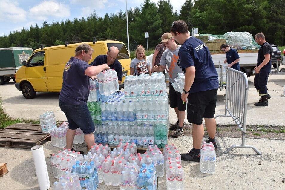 Feuerwehrleute beim Beladen der Hilfsgüter am ehemaligen Grenzübergang Altenberg. Abgepacktes Wasser gehörte auch dazu.