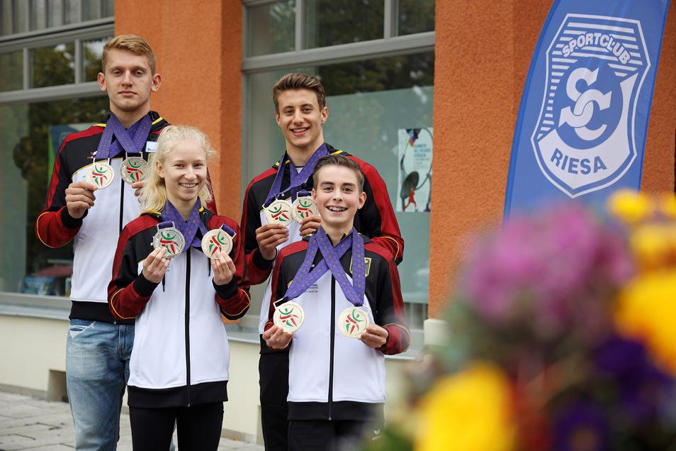 Daniel Blintsov, Pia Schütze, Tobias Vitera und Albrecht Kretzschmar präsentieren vor dem Vereinshaus des SC Riesa ihre EM-Medaillen.