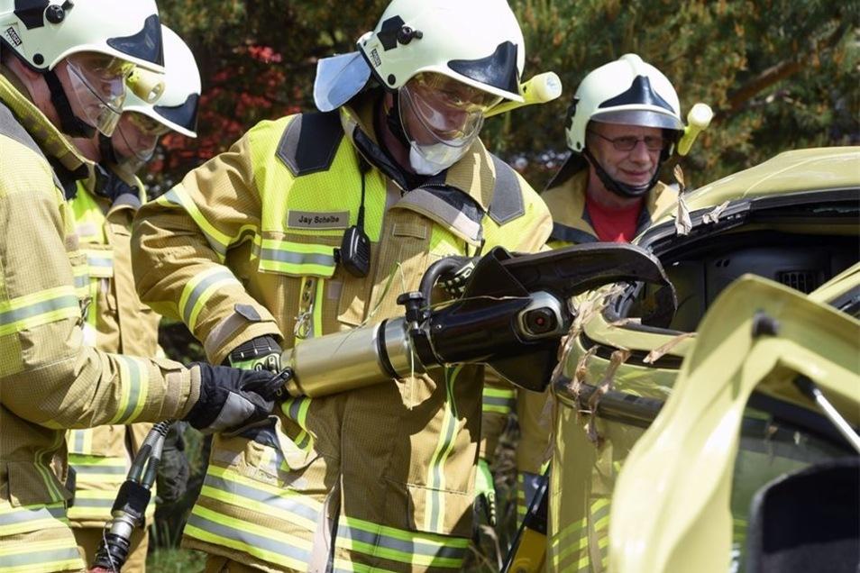 Die Kameraden öffnen den Kleinwagen mit der Rettungsschere.