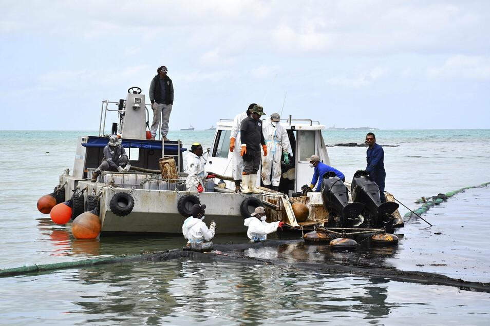 Arbeiter versuchen die Ausbreitung eines Ölteppichs zu verhindern.