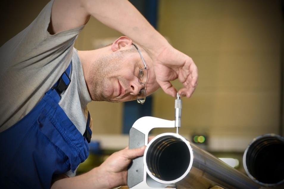 CNC-Dreher Rico Kaiser bei einer Kontrollmessung für ein Zylinderrohr.