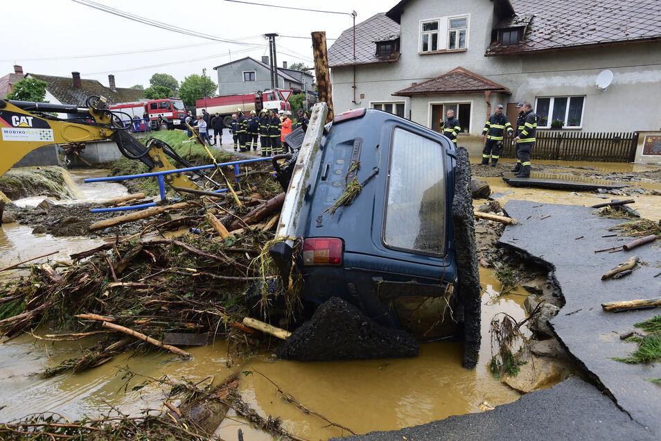 Feuerwehrleute stehen vor den Trümmern eines Autos nach einer schweren Überschwemmung in der Region Olmütz,