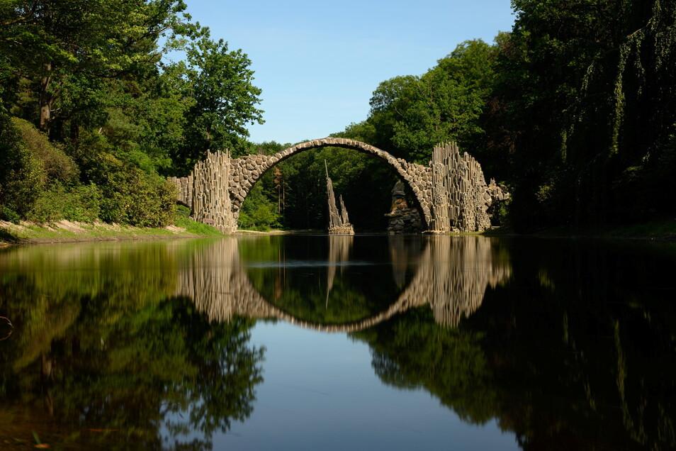 Die Rakotzbrücke bildet einen steinernen Kreis mit dem Wasser im See des Azaleen- und Rhododendren-Parks in Kromlau.
