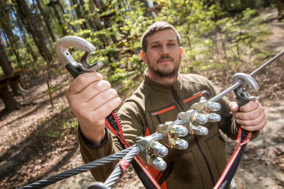 Marcel Schneider zeigt die neuen Sicherheitshaken, die die Besucher des Kletterwaldes noch besser vor einem Sturz schützen.