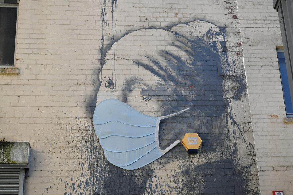 """Das Wandgemälde """"Das Mädchen mit dem Perlenohrring"""" von Banksy in Bristol hat eine Gesichtsmaske bekommen."""