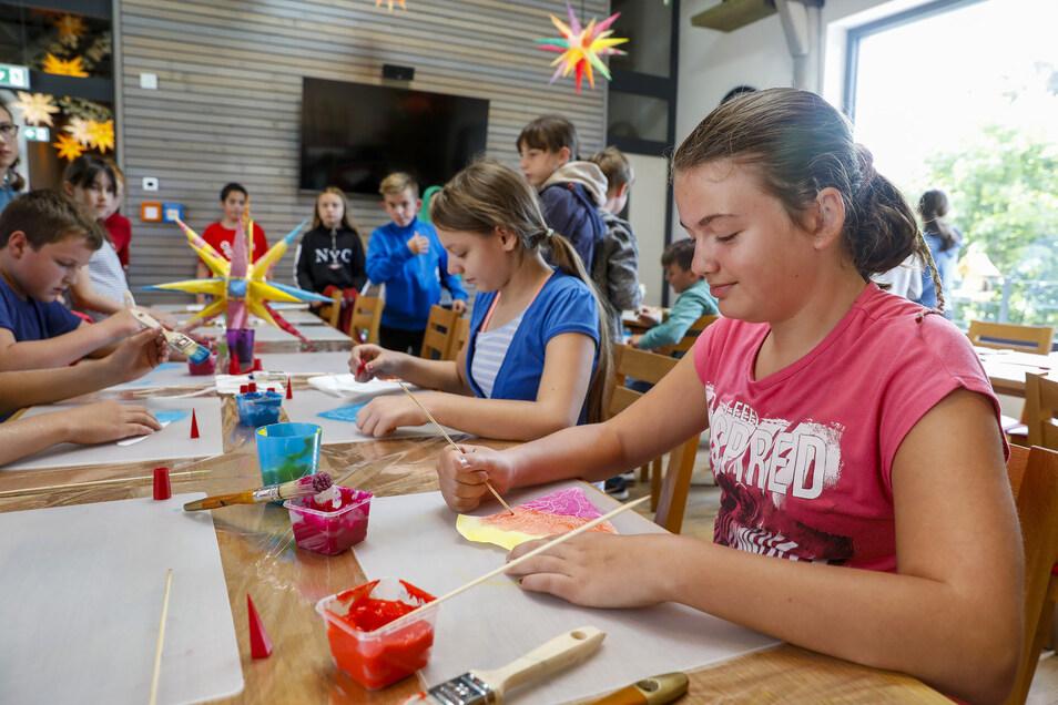 Lilly (rechts) und Anna (2. von rechts) bemalen und gestalten mit ihren Mitschülern die Zacken der Sterne, die dann in Klassenräumen und Schulflur hängen werden.