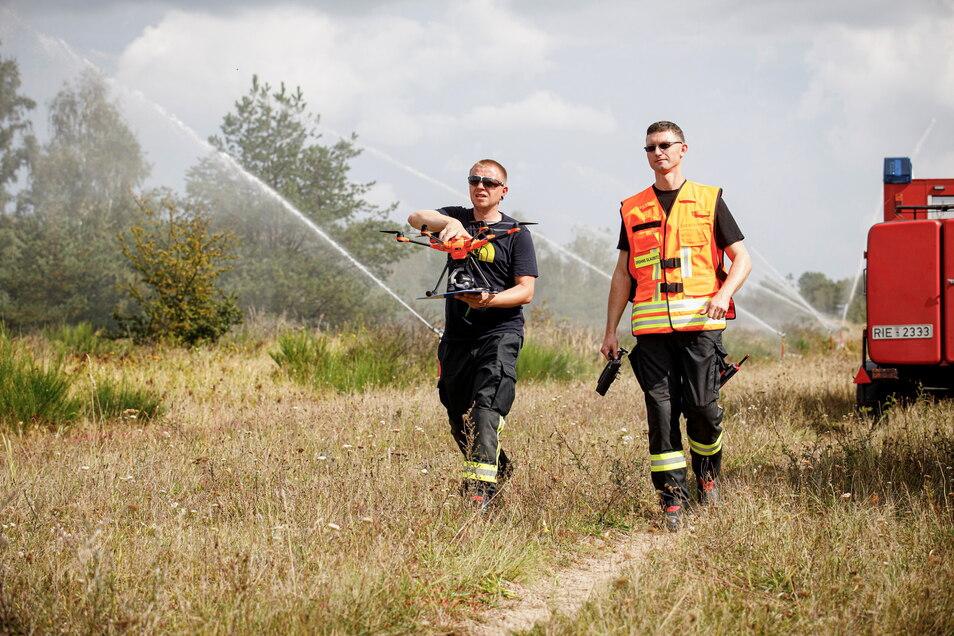 Glaubitzer Feuerwehrleute holen die Drohne herbei, um den Einsatz in der Gohrischheide aus der Luft zu beobachten.