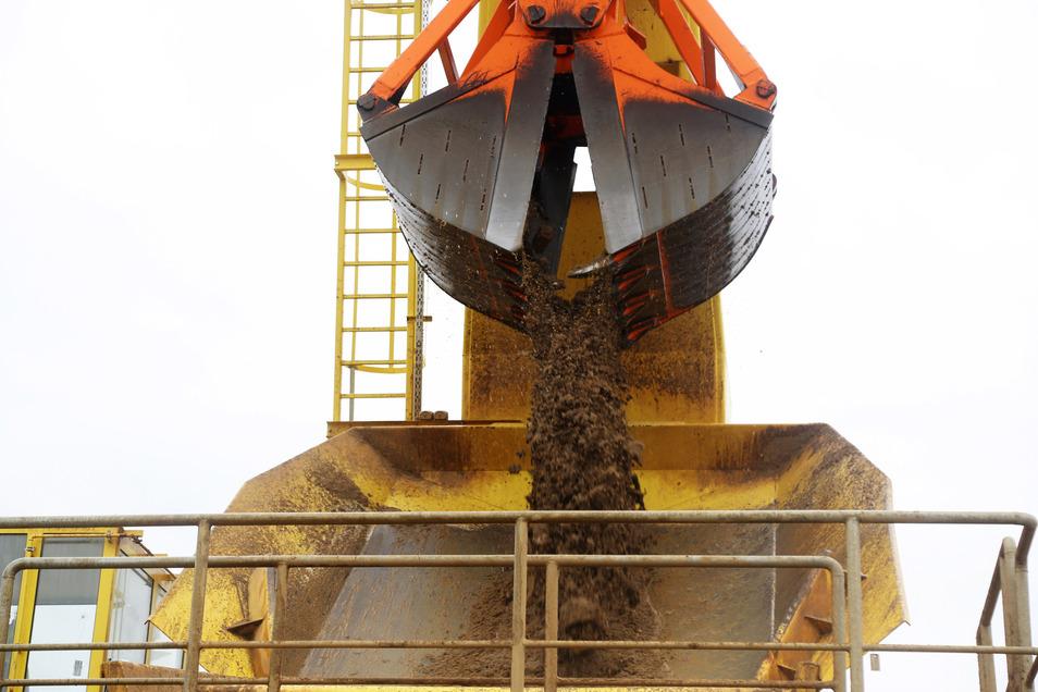Polternd entleert sich die Schaufel auf eine Rutsche, anschließend wird gesiebt.