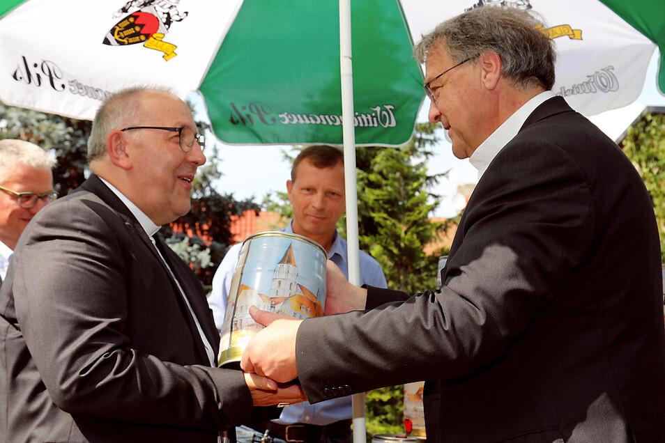 Nicht alltägliche Gabe für Bischof Wolfgang Ipolt (links): Der Wittichenauer Pfarrer Dr. Wolfgang Kresak verehrte ihm ein Fünf-Liter-Fässchen Wittichenauer Pilsner. Bürgermeister Markus Posch sah's mit Wohlgefallen – auch das ist schließlich Wir