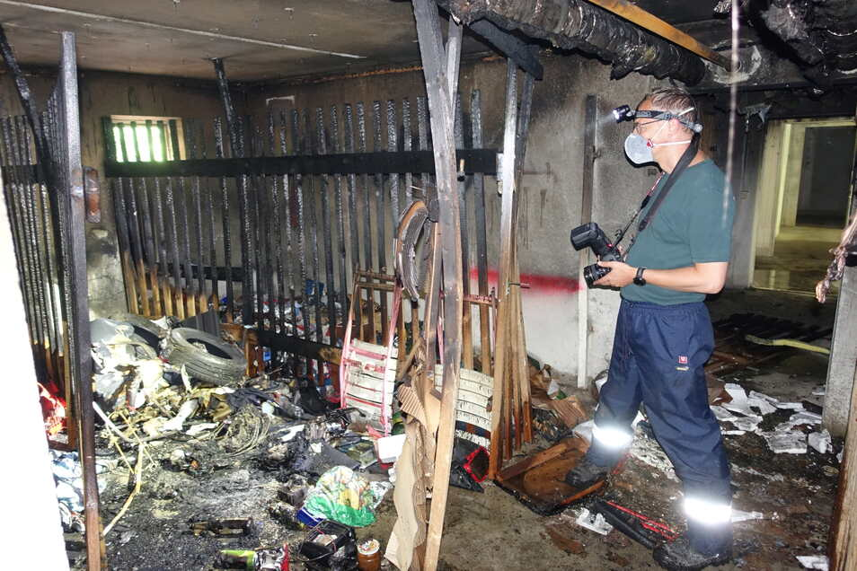 Ein Brandursachenermittler der Polizei macht im ausgebrannten Keller des Hauses Straße der Jugend 1 in Döbeln Nord Fotos.