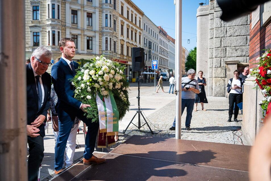 Landrat Bernd Lange (li.) und Sachsens Ministerpräsident Michael Kretschmer legen einen Blumenkranz an der Gedenktafel zum Volksaufstand nieder.