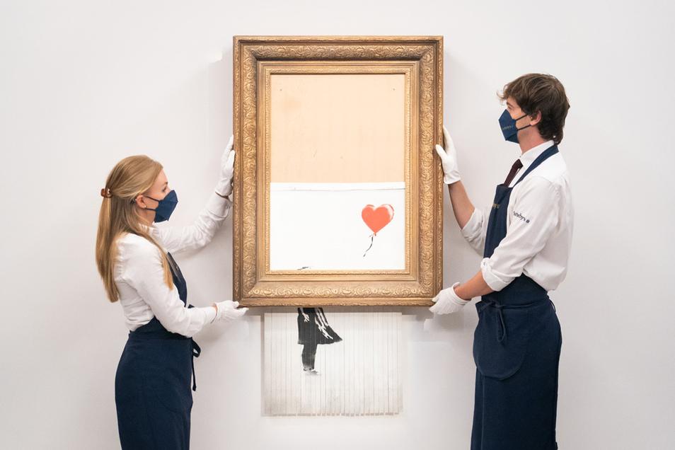 """Kunsthändler halten das Bansky-Werk """"Love Is In The Bin"""". Ursprünglich """"Girl With Balloon"""" genannt, wurde es 2018 während einer Auktion von Banksy teilweise geschreddert. Der Künstler benannte sein berühmtes Bild danach um."""