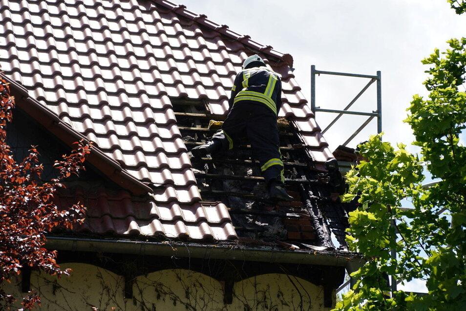 Bei dem Brand in Großpostwitz deckten Feuerwehrleute einen Teil des Daches ab, um an versteckte Glutnester heranzukommen.