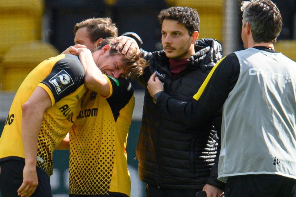 Tim Knipping liegt in den Armen von Chris Löwe, auch Philipp Hosiner tröstet Dynamos Verteidiger.