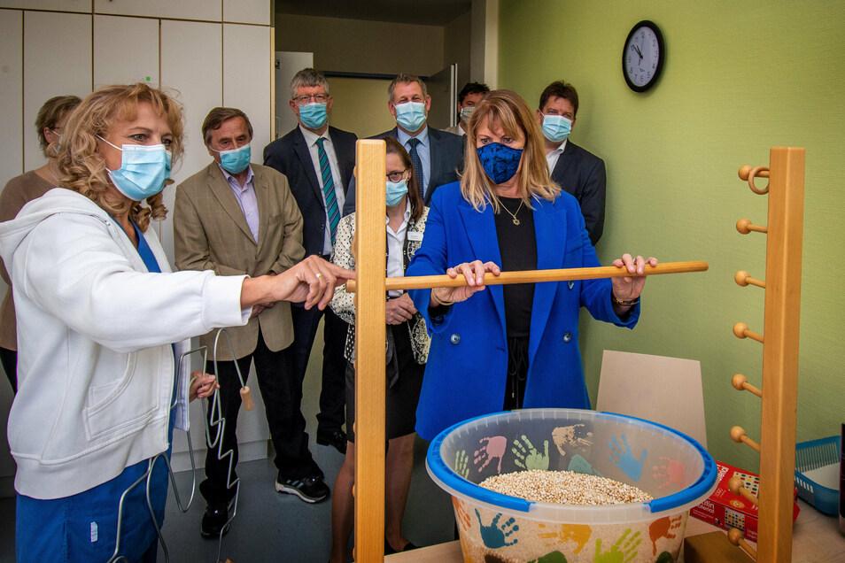 Ergotherapeutin Roswitha Annekathrin Stephan  zeigt Sachsens Gesundheitsministerin Petra Köpping, wie sie Patienten hilft, motorische Fähigkeiten wie das Greifen zurückzuerlangen.