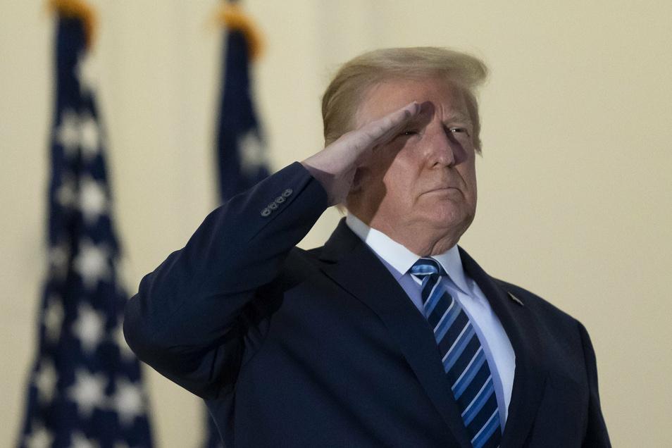Trump salutiert auf dem Balkon des Blue Room bei seiner Rückkehr in das Weiße Haus, nachdem er das Krankenhaus verlassen hat.