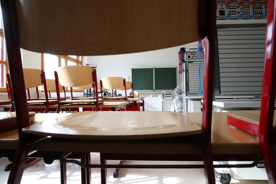 Stühle auf den Bänken in einem leeren Klassenzimmer. Ab Montag schließen wieder die Schulen im Landkreis Meißen, mit Ausnahme der Abschlussklassen. Da die Inzidenzwerte hoch sind, wird die Schließung wohl noch eine Weile andauern.
