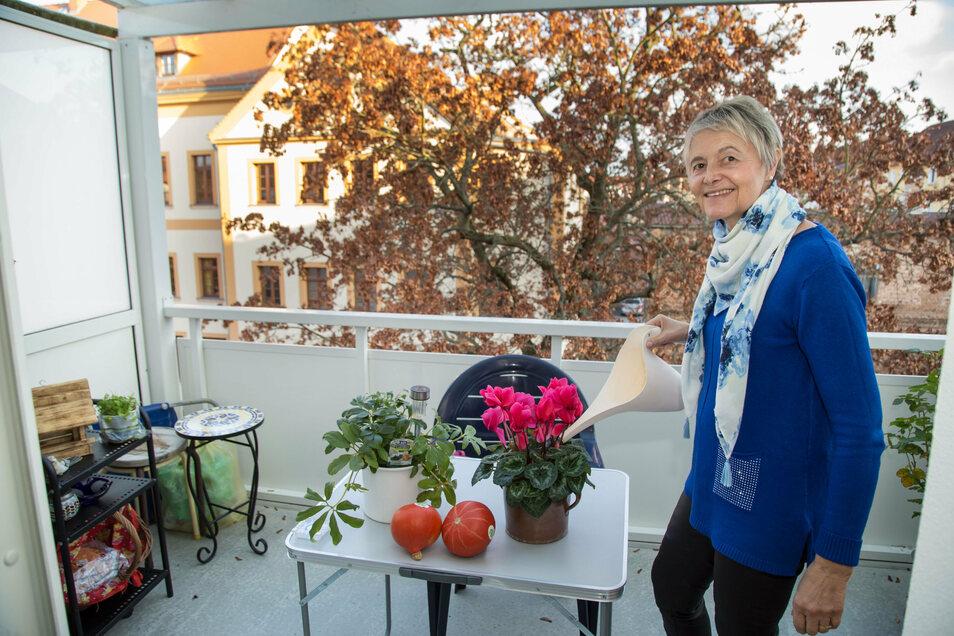 Christiane Schöler genießt den Balkon und von ihm den Blick zum Gymnasium. Im Sommer ist das Gebäude vom Grün der Blätter verdeckt.