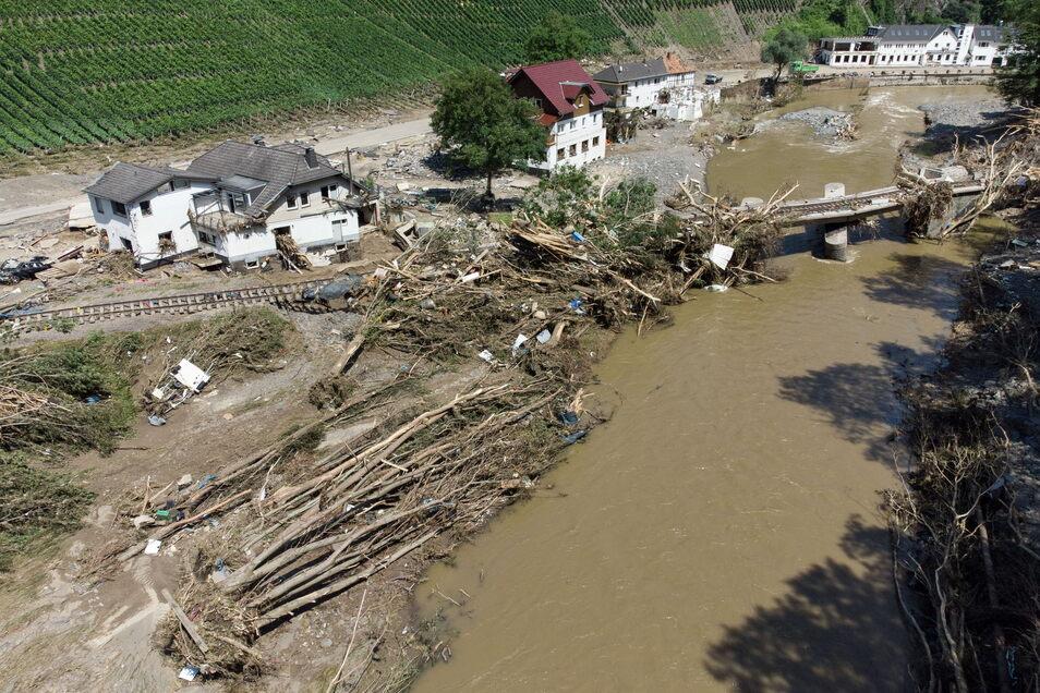 Entwurzelte Bäume liegen neben komplett zerstörten Häusern am Ufer der Ahr.