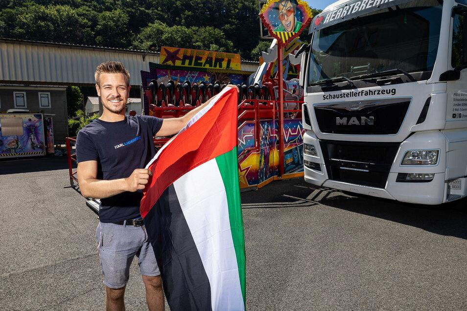 Oktoberfest goes Dubai! Und Schausteller Philipp Wiemer aus Freital geht mit. Hier zeigt er schon mal die Flagge der Vereinigten Arabischen Emirate, zu der die Glitzermetropole gehört.