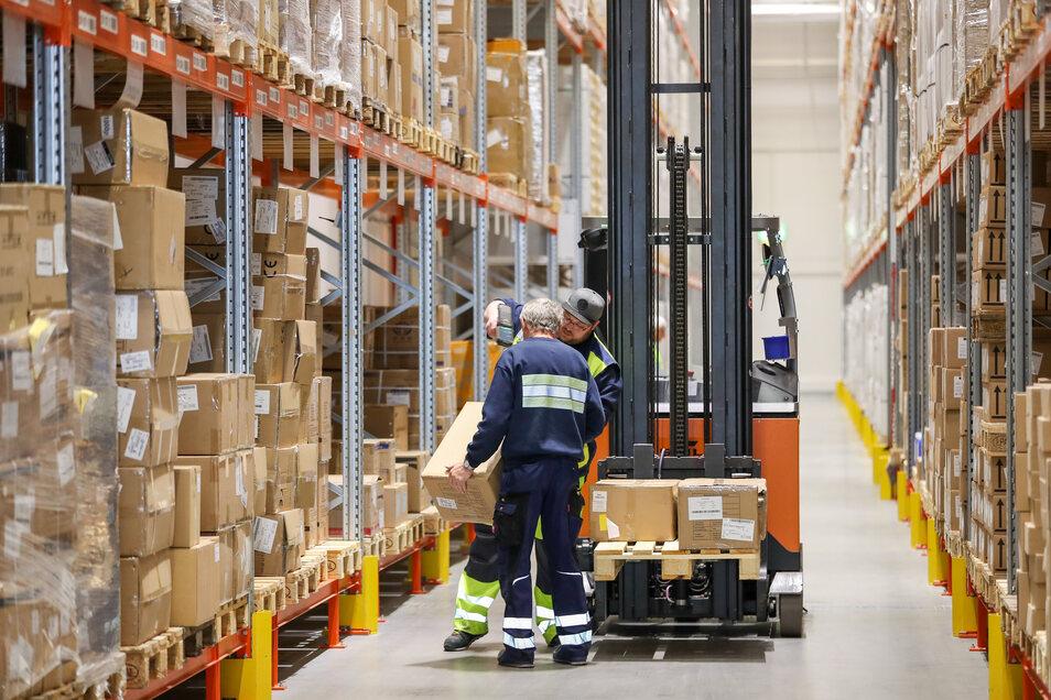 Mitarbeiter des Logistikunternehmens Kühne & Nagel sortieren im Wareneingang Kartons mit Schutzmasken.
