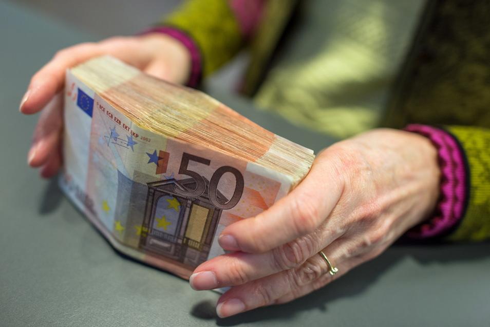 Eine Bank-Mitarbeiterin hält am Schalter einer Sparkasse in München 5.000 Euro in 50-Euro-Scheinen in den Händen.