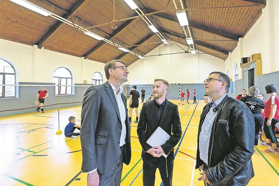 Der Blick geht nach oben: Sachsens Innenminister Roland Wöller, Vereinschef Andreas Demel und der Kleinnaundorfer Stadtrat Steffen Üregi (v. l.) schauen sich das marode Dach der Turnhalle an.