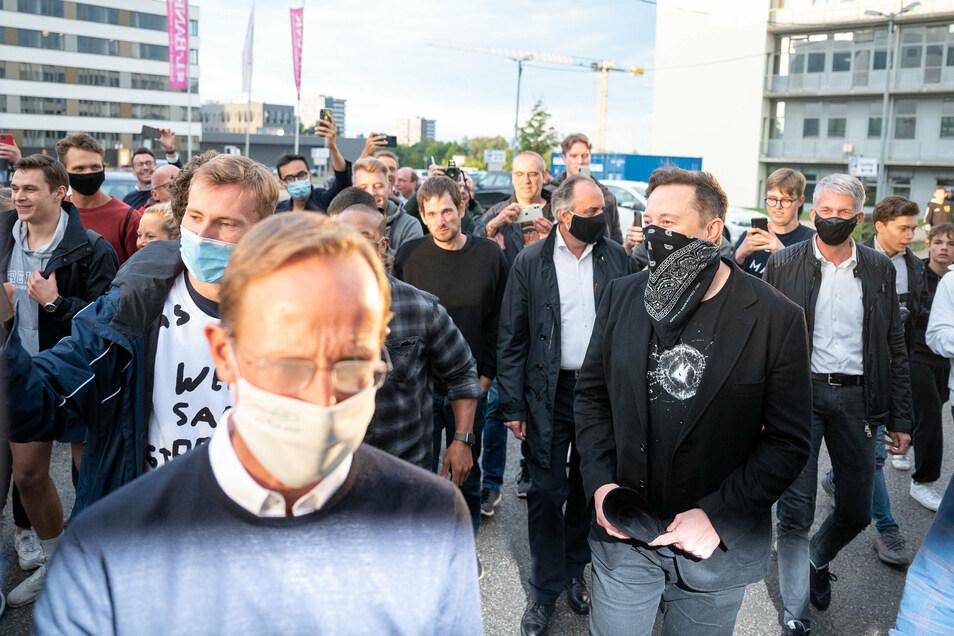 Elon Musk (vorn r, schwarz-weißes Tuch als Mund-Nasen-Schutz) in Tübingen, vor ihm geht Franz-Werner Haas (l), Vorstandsvorsitzender von Curevac.