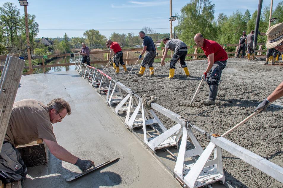 Der sogenannte Rüttelbalken gab den Brückenkörper auf der Oberseite die endgültige Form. Mit umgedrehten Harken wurde der Beton verteilt.