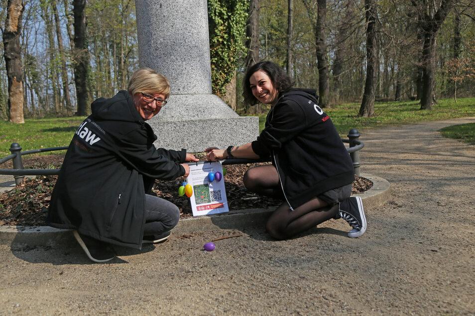 Kaum zu übersehen: Anja Müller und Sandra Jeske von Outlaw bringen im Riesaer Stadtpark Hinweise für einen ungewöhnlichen Osterspaziergang an.
