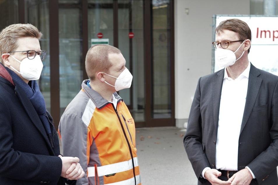 Sachsens Innenminister Roland Wöller (r.) informiert sich beim Leiter des Impfzentrums in Pirna-Jessen, Christian Thie (M.) und dem Vorsitzenden des DRK Pirna, Oliver Wehner.