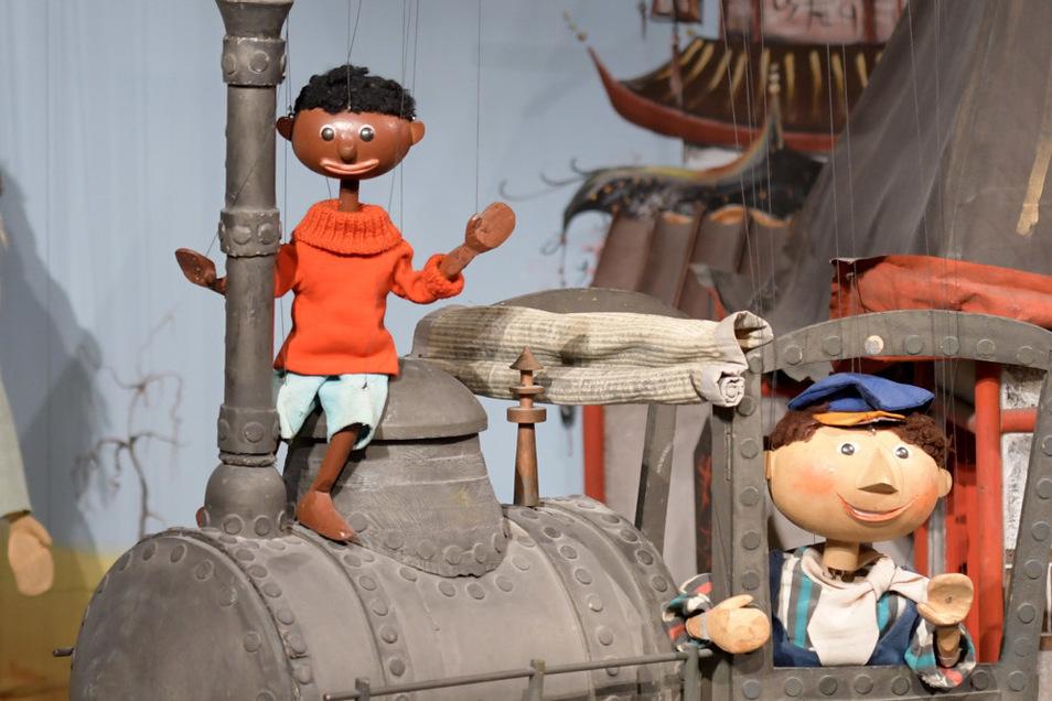 """Jim Knopf auf Lok """"Emma"""" und Lukas der Lokomotivführer. Die Realität bei der Bahn ist nicht so märchenhaft wie in der Augsburger Puppenkiste."""