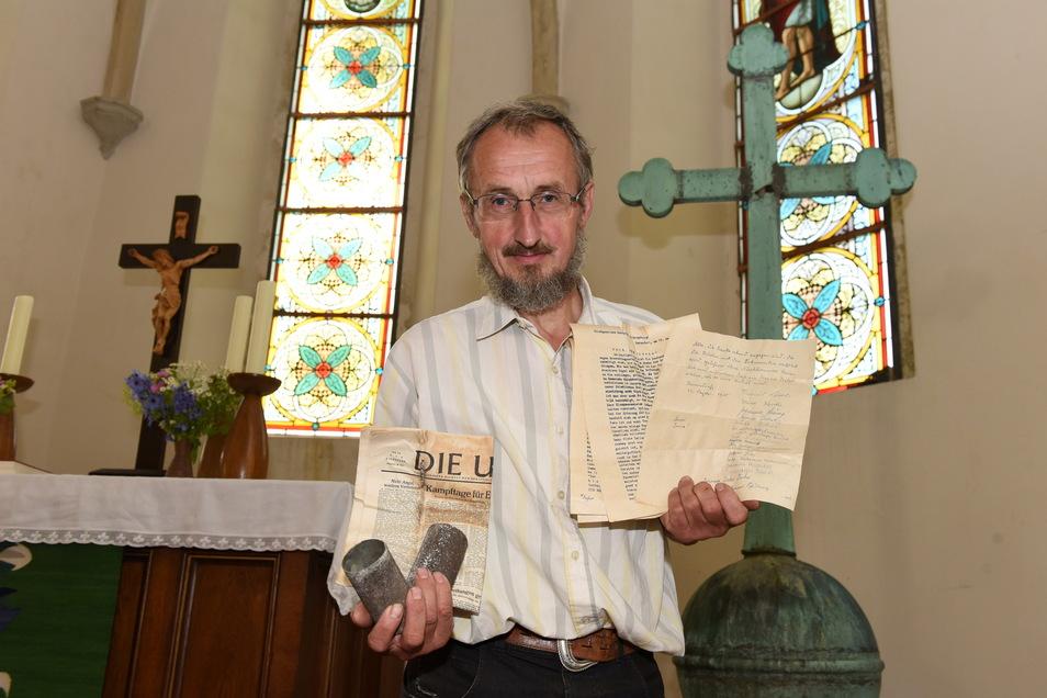 Eine wichtige Aufgabe war für Pfarrer Gerd Trommler in Hermsdorf/E. die Sanierung des Dachs. Hier zeigt er die Dokumente, die dabei 2018 in einer Zeitkapsel gefunden wurden.