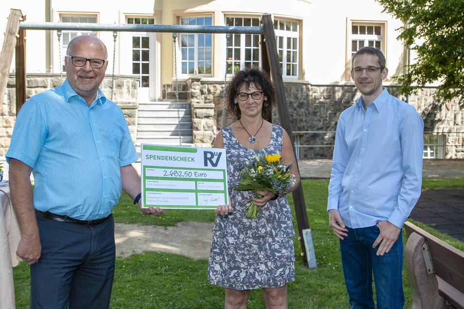 Der regionale SZ-Geschäftsführer Jörg Seidel (li.) und der Freitaler Redaktionsleiter Tilman Günther (re.) übergeben einen Spendenscheck an Heimleiterin Sybille Clemens im DRK Kinderheim Dorfhain.