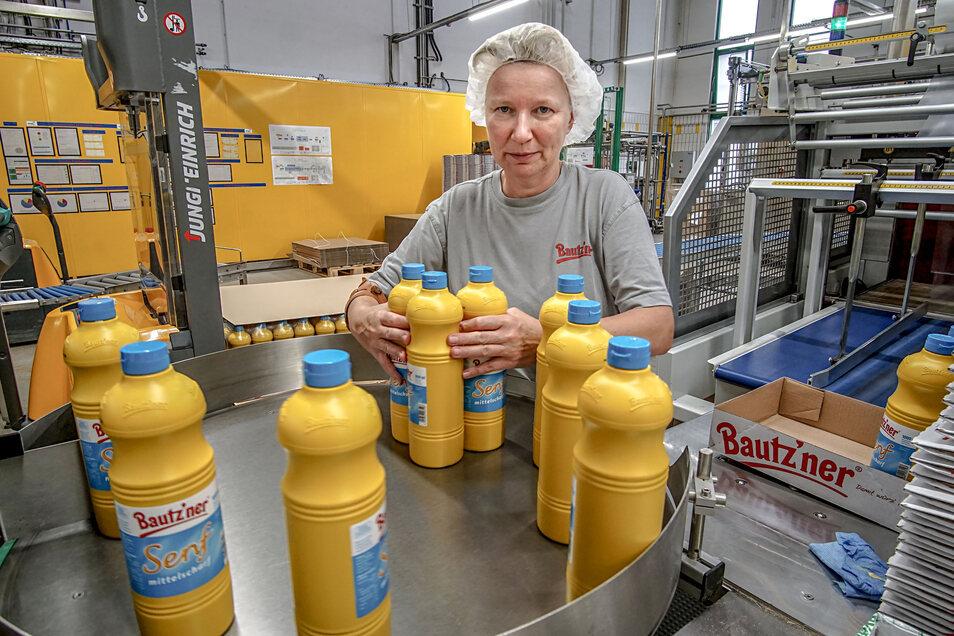 Sibylle Domagala arbeitet an der Verpackungslinie für Ein-Liter Flaschen. Täglich werden im Werk rund 90 Tonnen Senf abgefüllt.