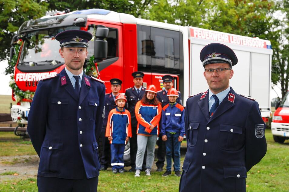 Steffen Fiedler (rechts), Tobias Zschierlich und Leutersdorfer Feuerwehrleute zeigen das neue Löschfahrzeug der Wehr.
