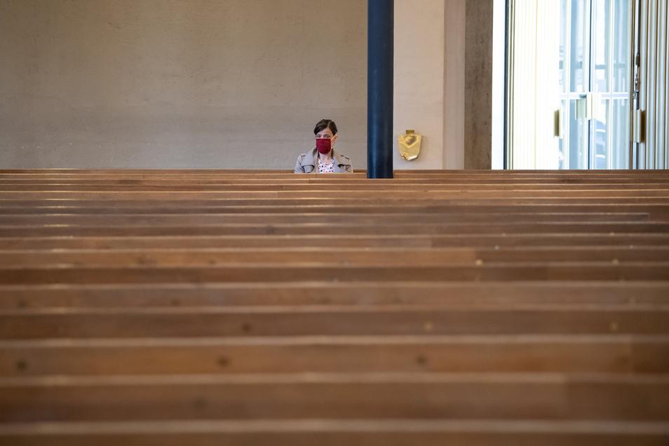 Bayern, München: Eine Frau mit Mundschutz verfolgt einen Gottesdienst in der ansonsten fast menschenleeren St. Matthäuskirche. Aufgrund der Corona-Krise wurde der evangelische Gottesdienst ausschließlich im Radio und Internet übertragen.