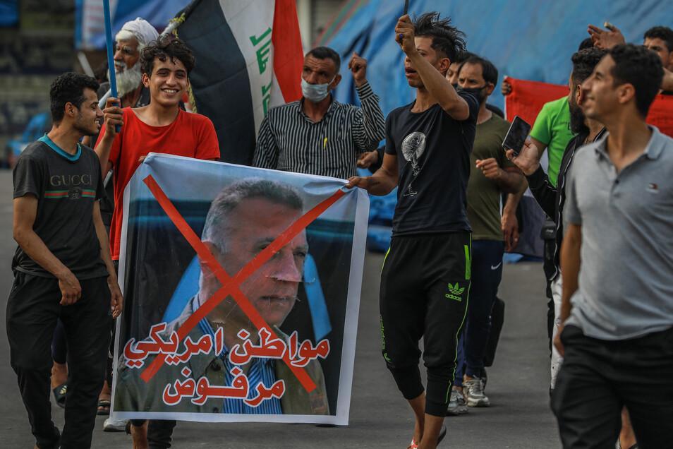 Teilnehmer eines regierungskritischen Protests halten ein Plakat mit einem durchgestrichenen Foto des derzeitigen Chefs des irakischen Geheimdienstes, al-Kasimi.