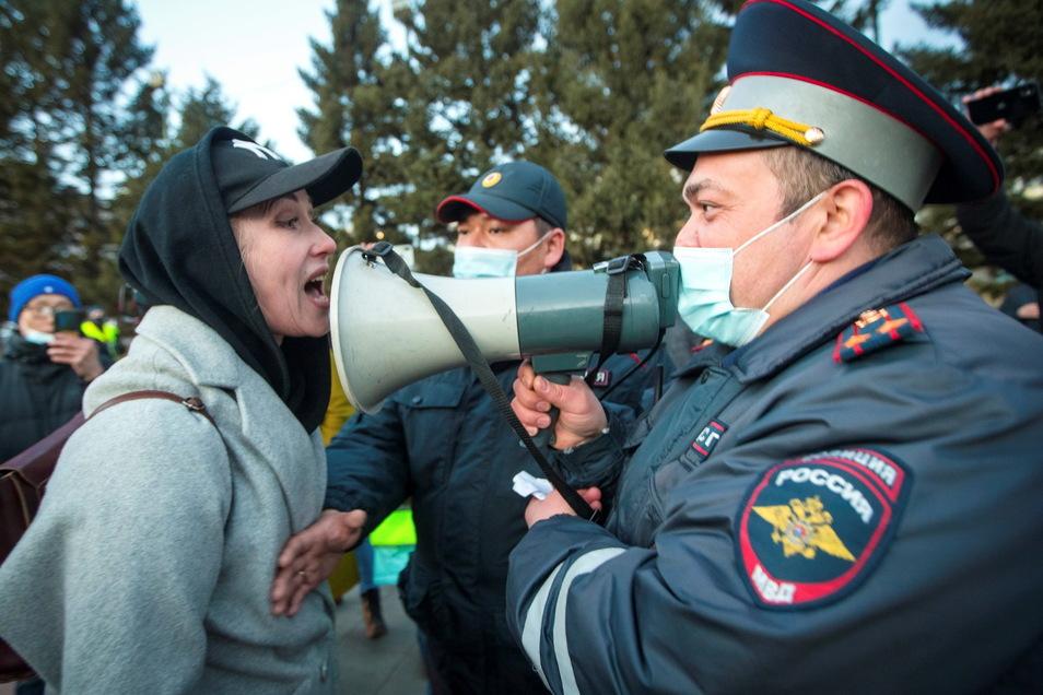 Eine Frau streitet während eines Protestes zur Unterstützung des inhaftierten Oppositionsführers Alexej Nawalny in Ulan-Ude, der regionalen Hauptstadt von Burjatien, einer Region nahe der russisch-mongolischen Grenze, mit einem Polizisten.
